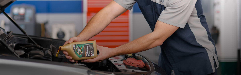 service technician pours oil in car engine