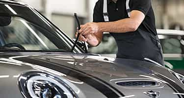 Certified MINI Technician performs routine vehicle maintenance